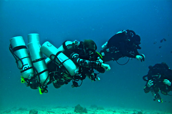 technical diver with lots of scuba tanks